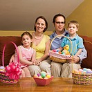 Caucasian family on couch holding Easter basket and looking at viewer.