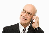 Caucasian middle-aged businessman talking on cellphone smiling against white background.