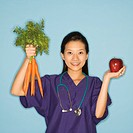 Asian Chinese mid-adult female doctor holding up bunch of carrots with one hand and red apple in other against blue background smiling and looking at ...