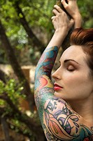 Nude tattooed Caucasian woman in forest leaning on tree