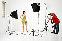 Model being photographed in studio by a male photographer
