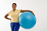 Woman standing and holding exercise ball