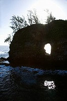 Rock with hole in it in Pacific ocean off island of Maui, Hawaii