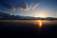 Aerial of sun setting over Pacific ocean with clouds