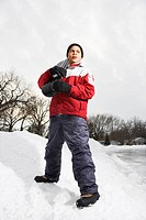 Boy standing holding snowboard in snow.