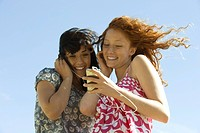 Two young women outdoors, listening to MP3 player together