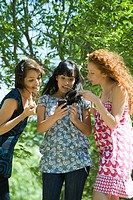 Three young women standing outdoors, looking at smartphone