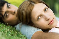 Young couple lying on grass, looking at camera, close_up