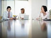 Three businesspeople having meeting in conference room low angle view