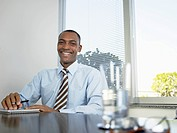 Businessman laughing by table portrait (thumbnail)