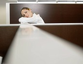 Office worker leaning against partition wall portrait
