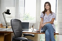 Young entrepreneur sitting on desk portrait (thumbnail)
