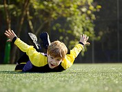 Young boy lying on grass