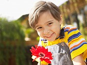 Boy with red gerbera daisy portrait