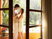 Young couple hugging on doorway