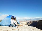 Young couple sitting in tent by cliff, Moab, Utah, USA