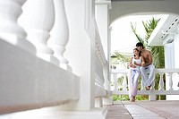 Young couple with mugs standing on terrace low angle view