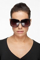 Mid adult woman wearing oversize sunglasses, portrait