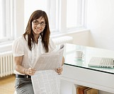 Mid_Adult Woman Reading Newspaper in Office
