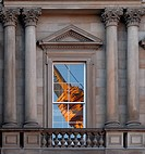 Close up yellow crane reflected in window of 19c classical facade