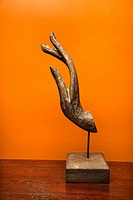 Carved hand sculpture from Thailand against orange wall.
