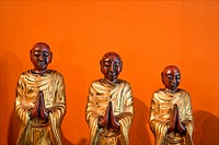 Three wooden statues of Buddhist disciples against orange wall