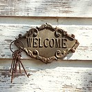 Welcome sign and metal keys on old white peeling building (thumbnail)