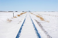 Railroad tracks in snow covered rural landscape