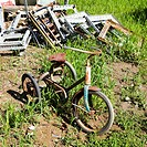 Old abandoned tricycle in grassy field next to junk pile