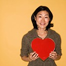 Pretty mid adult Asian woman holding red heart shaped box