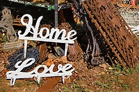 Metal garden decorations of words Love and Home next to rusted metal objects