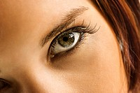 Close up of young Caucasian woman's green eye with makeup