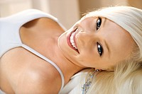 Portrait of attractive blonde Caucasian young adult woman lying down smiling and looking at viewer