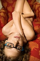 Nude Caucasian young adult woman lying upside down covering herself and looking at viewer.