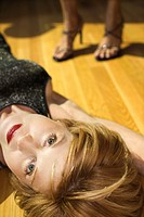 Caucasian mid adult woman lying on wood floor looking at viewer with feet of another woman in background wearing heels