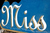 Blue sign with the word 'Miss' in cursive written on it