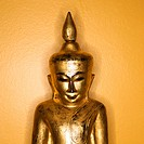 Golden wooden Buddha statue from Burma against yellow wall