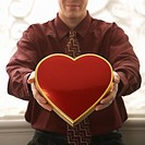 Mid adult Caucasian man holding a heart shaped box of chocolates at viewer