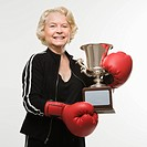 Caucasian senior woman wearing boxing gloves holding trophy