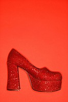 Red glitter high heel shoe against red background