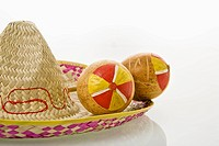 Pair of handmade Mexican maracas percussion musical instruments on sombrero straw hat (thumbnail)