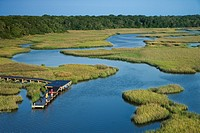 Aerial view of two teenage boys fishing from dock in marshy lowlands of Bald Head Island, North Carolina