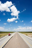 High angle view of highway with tractor trailer truck and blue cloudy sky.