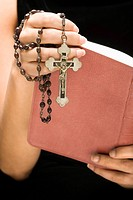Woman holding Holy Bible open with rosary and crucifix in hand