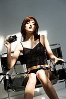 Portrait of attractive young redhead Caucasian woman in lingerie holding vintage camera