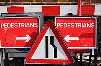 Traffic roadwork signs stacked together on a pavement
