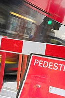 A London bus rushing past a roadside construction barrier