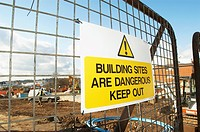 Construction site with danger sign hanging on the access gate