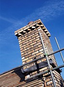 Detail of brick built chimney and scaffolding showing lead flashing at roof junction