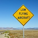 Low flying aircraft sign alongside desloate highway